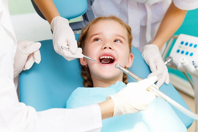 Young girl in dentist chair having her teeth checked