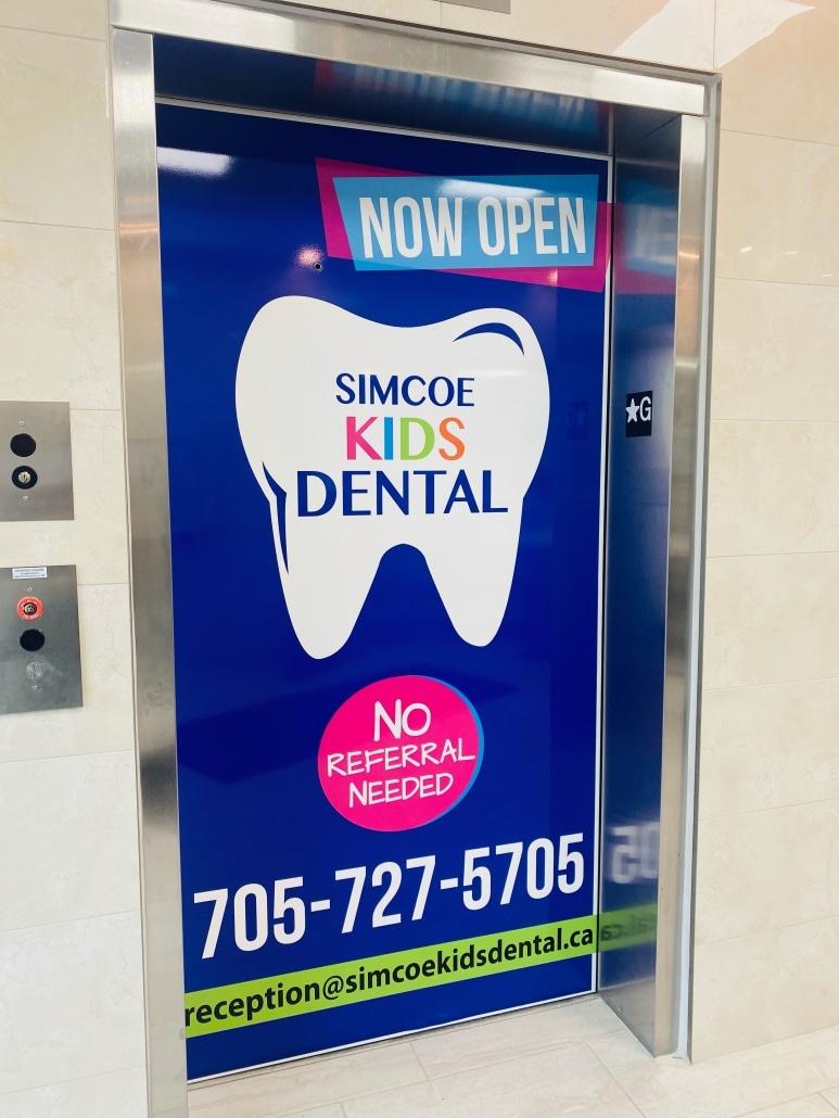 Elevator door ad for Simcoe Kids Dental - Now Open